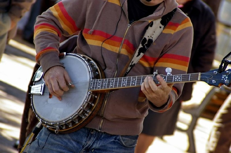Someone tunes the banjo 1 string at a time